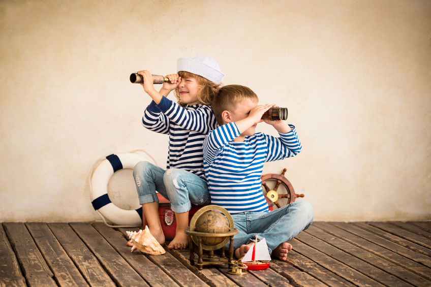 37128340 - children playing with vintage nautical things. kids having fun at home. travel and adventure concept. retro toned image