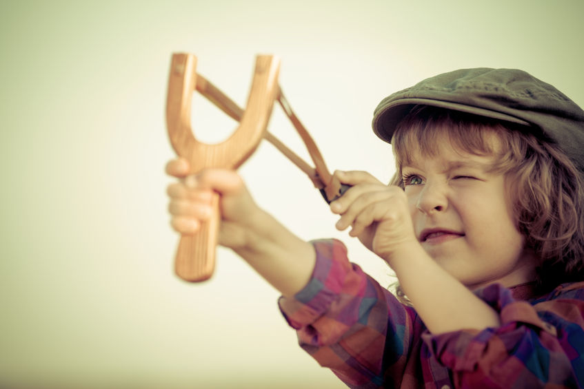 26818999 - kid holding slingshot in hands against summer sky background. retro style
